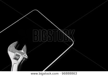 Adjustable Wrench On The Lcd Tablet Display Isolated On Black