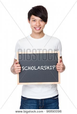 Young man hold with chalkboard showing a word scholarship