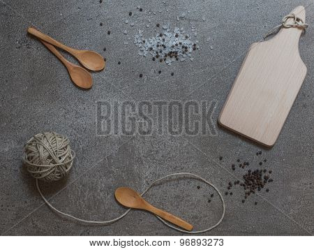Wooden Spoons, Cutting Board And Clew On The Stone Background