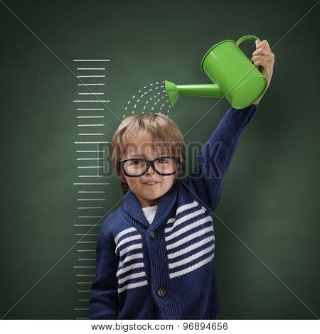 Young boy trying to make himself taller with watering can measuring his growth in height against a blackboard scale
