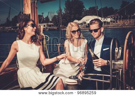 Stylish wealthy friends having fun on a luxury yacht