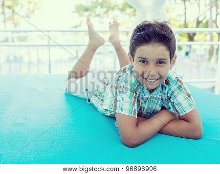 Cute kid enjoying on turquoise bed