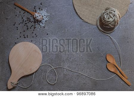 Wooden Spoons, Cutting Board And Knot On The Stone Background