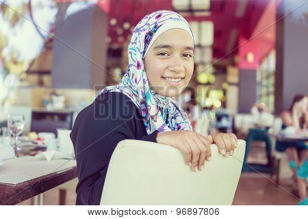 Happy Muslim family in restaurant
