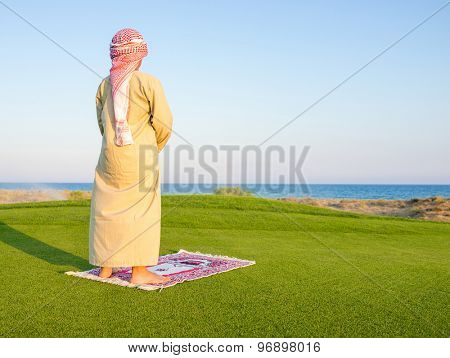 Muslim Arabic boy praying on green meadow