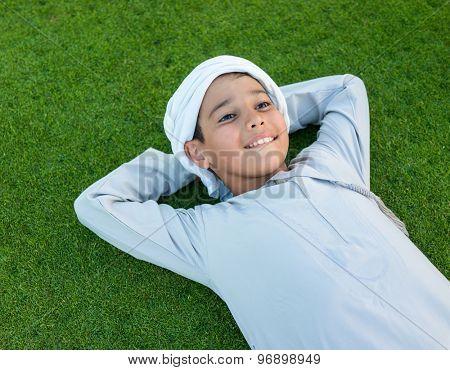 Happy Arabic kid on green grass