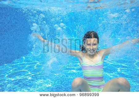Girl jumps and swims in pool underwater, happy active child has fun in water, kid sport