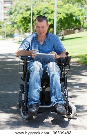 Happy Disabled Man Using Tablet At The Park