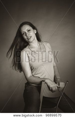 Portrait of long-haired young woman sitting on a chair. Black and white photo