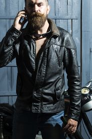 stock photo of biker  - Handsome brutal unshaven sexy male biker in brown leather jacket blue jeans and sun glasses standing in garage near motor cycle holding mobile phone and speaking on wooden background vertical picture - JPG
