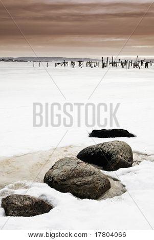 Pier And Stones In Frozen Sea