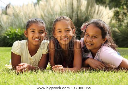 Happy girl friends lying in grass
