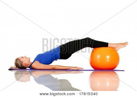 Sportive woman exercising with a pilates ball - isolated over white