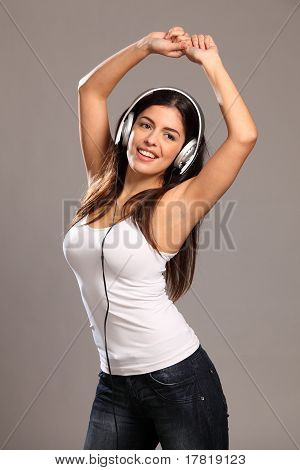 Happy young girl dancing to music