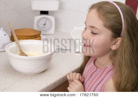 Pretty young girl anticipating helping with icing the cake – focus on girl