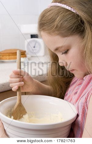 Little girl with mixing bowl in kitchen helping with baking