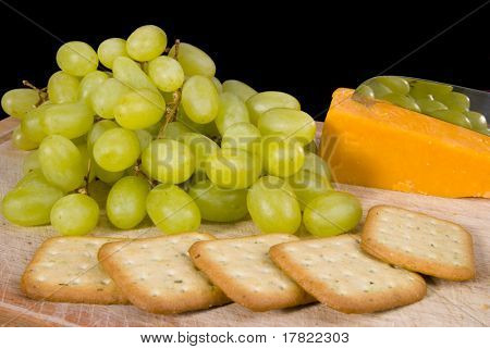 Still life of fruit and cheese with crackers on wooden board