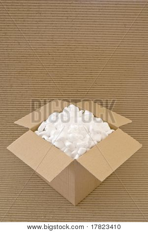 Cardboard carton filled with packing chips on a corrugated board background