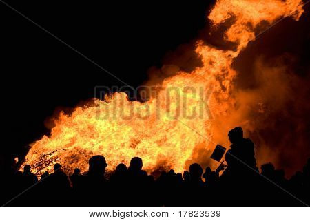 Crowd in silhouette enjoying a large bonfire