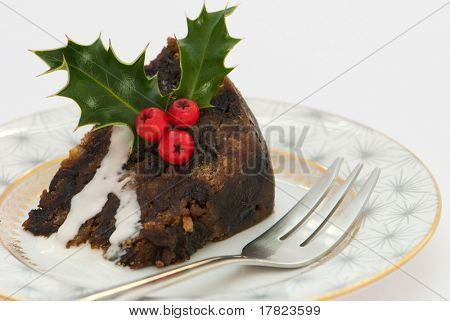 Slice of Christmas pudding with fork & decorated with holly