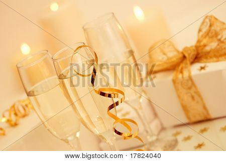 Champagne for Christmas with lit candles in the background set at an angle - gold theme
