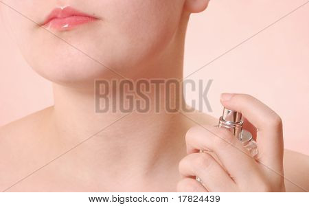 Young woman applying fragrance to her neck