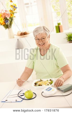 Happy elderly woman eating healthy salad at home. Looking at camera, smiling.?