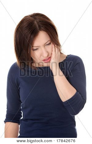 Attractive woman in her 40s pressing her bruised cheek with a painful expression as if she's having a terrible tooth ache.
