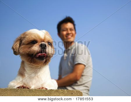 Young man sitting with his dog in outdoor