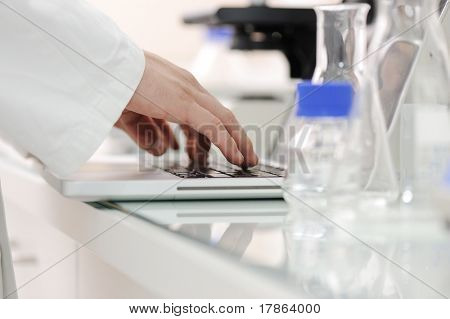 Scientist working at lab with laptop, microscope and tubes