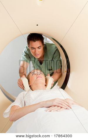 A young woman having a CT scan taken - Nurse getting things prepared