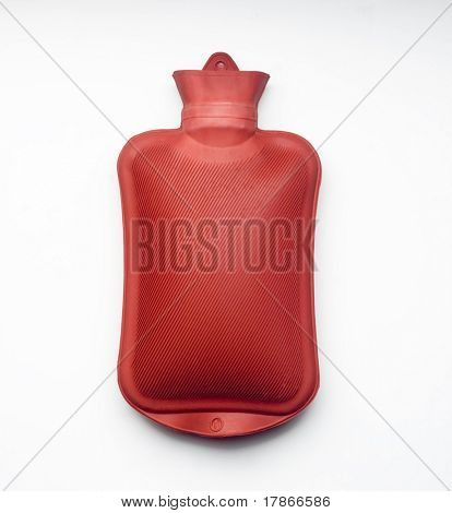 Red hot water bottle made of rubber in front of a white background.