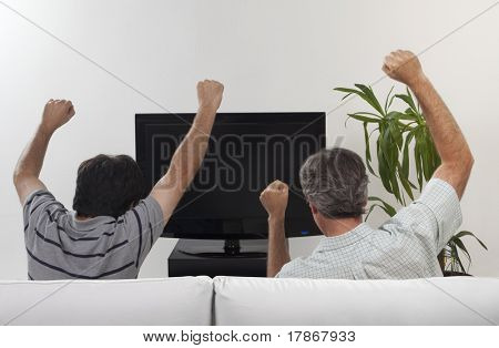 Two friends celebrating some event watching a flat tv set sitting on a sofa