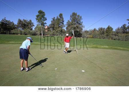 Father And Son Golfing On Green