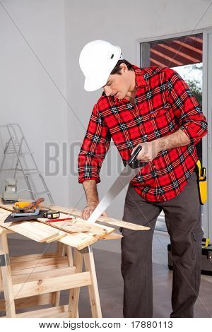 A wood worker using a hand saw in a home interior