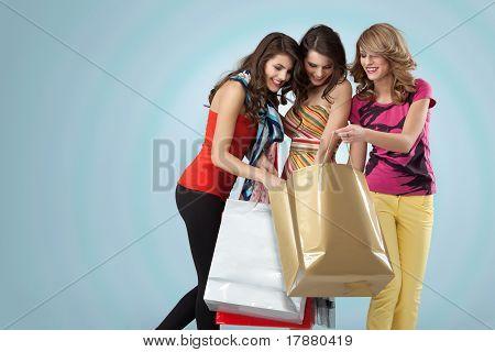 Studio Bild drei schöne junge Frauen halten suchen überrascht lächelnd Einkaufstaschen