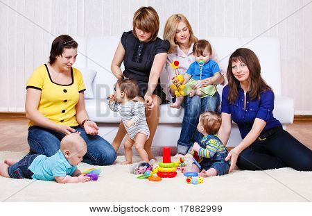 Mothers in the living room look at their babies playing
