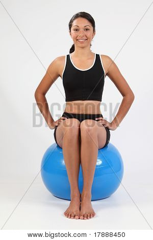 Fit young woman balancing on blue exercise ball