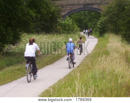 Family Cycling On A Trail