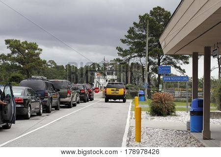 Southport NC USA - September 29 2016: People in vehicles waiting to drive onto the Southport Ferry in the day. Autos with people ready to board the ferry.