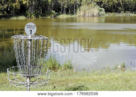 Oakland Park FL USA - November 8 2016: Easterlin Park Frisbee Golf sign on a goal post basket target by a lake. Disc golf basket hole and sign on a sunny day.
