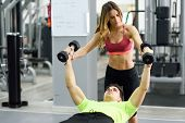 Personal Trainer Helping A Young Man Lift Weights poster