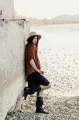 Постер, плакат: Beautiful Stylish Boho Woman With Hat Leather Bag Fringe Poncho And Boots Girl In Gypsy Hippie Lo