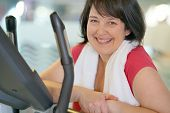 Overweight woman at the gym doing cardio exercises on bike poster