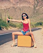 picture of old-fashioned  - Beautiful young lady with case hitching a ride on a lonely hot desert road - JPG