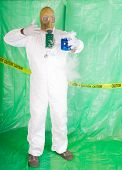 foto of decontamination  - Man in Hazmat clothing in temporary green plastic decontamination chamber wearing a gas mask and carrying toxic chemical that is exuding gaseous vapor - JPG