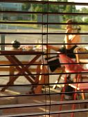 image of stripping women window  - view through blinds - JPG