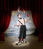 image of circus clown  - Clown performing on stage with red curtains - JPG