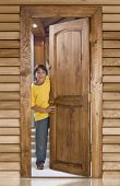 pic of front door  - Boy opening a wooden door in front of his home - JPG