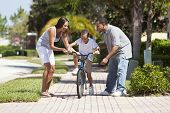 A young African American family with boy child riding his bicycle and his happy excited parents enco